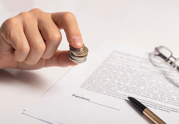 Продавец держит монеты в руке над контрактом с ручкой и очками