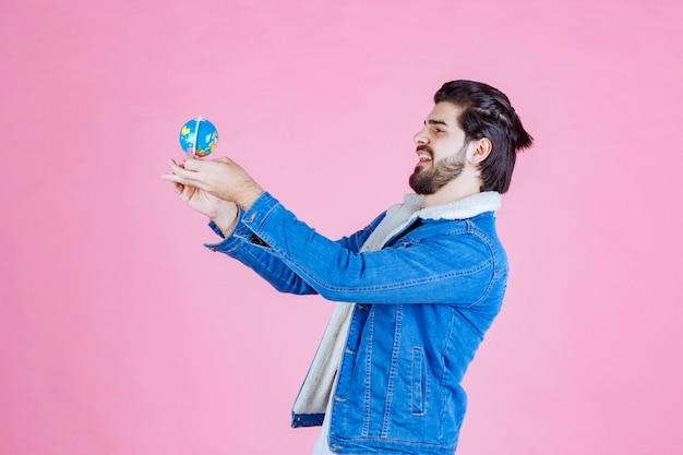Venditore in possesso di un mini globo e promuovere il prodotto