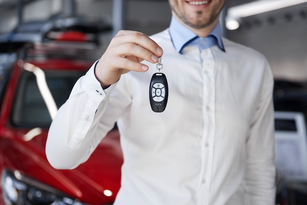 Salesman holding out car key in showroom