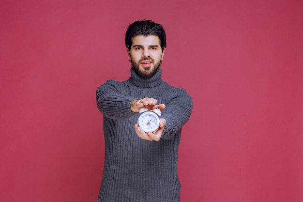 A salesman holding a white alarm clock and promoting it to the customer.