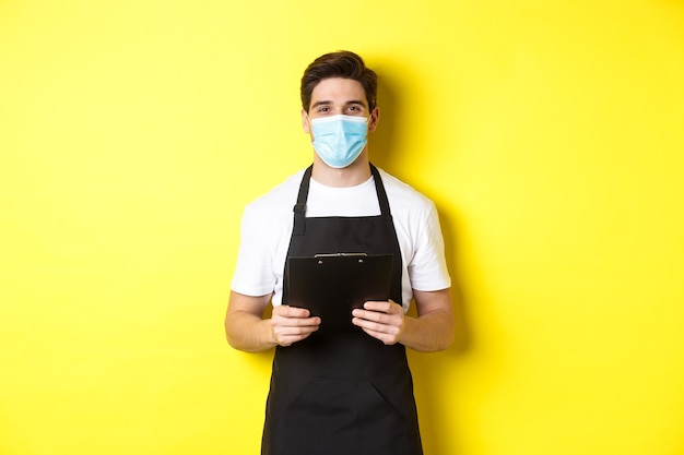 검은 앞치마와 의료 마스크 클립 보드를 들고 세일즈맨, 상점에서 일하고, 노란색 벽 위에 서