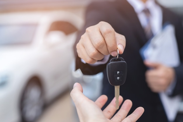 The salesman is delivering the new car keys to the customer at the showroom.