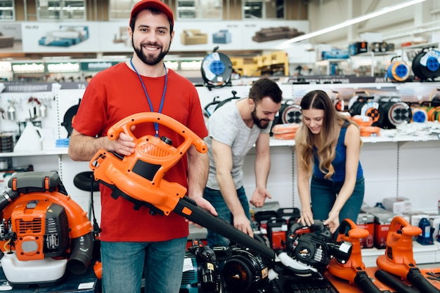Salesman is posing with new leaf blower with couple.