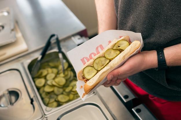 Salesman making hotdog in fast food snack bar