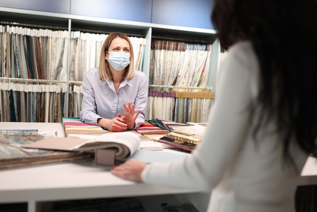 Salesman in medical mask advises client. safe service in coronavirus pandemic concept