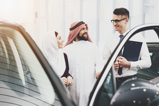 Salesman offers car credit for arab man and woman.