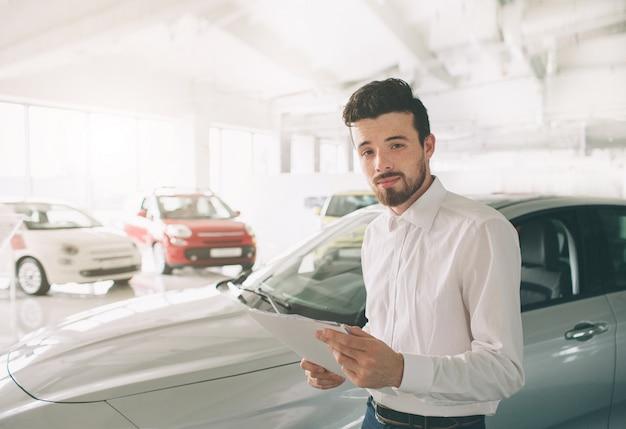 쇼룸에서 새 차를 제시하는 세일즈맨