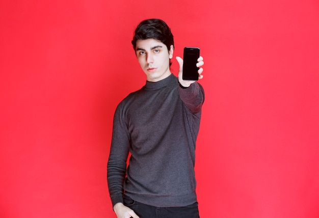 Salesman promoting and showing features of a new smartphone