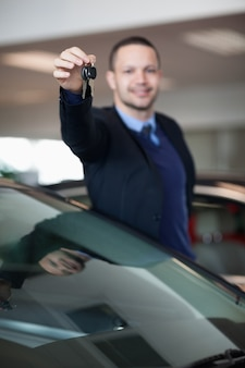 Salesman raising his arm while holding car keys