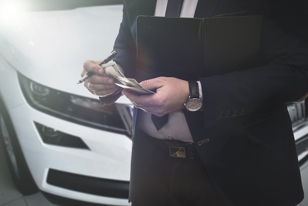 Salesman selling auto in car shop or businessman buying new car holding dollar in hand.