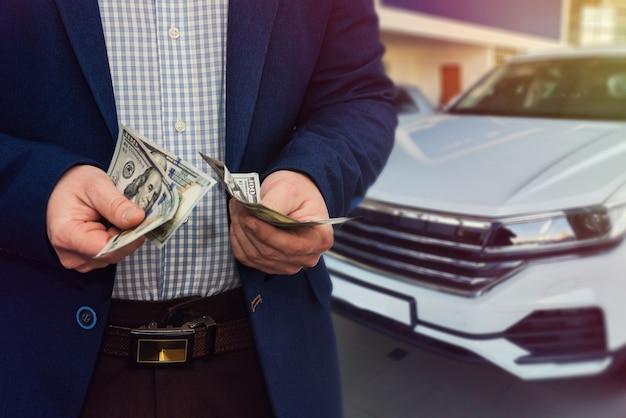 자동차 상점 또는 달러를 손에 들고 새 차를 구입하는 사업가 자동 판매 세일즈맨.