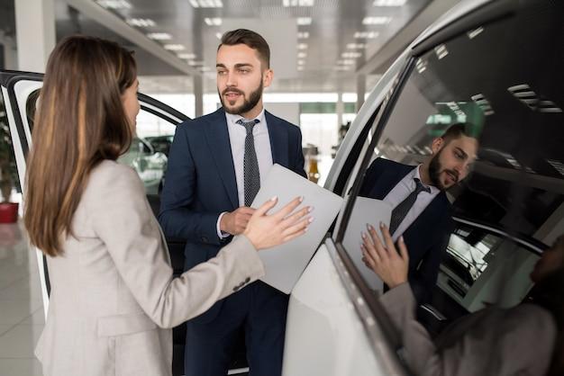 Salesman selling cars in showroom