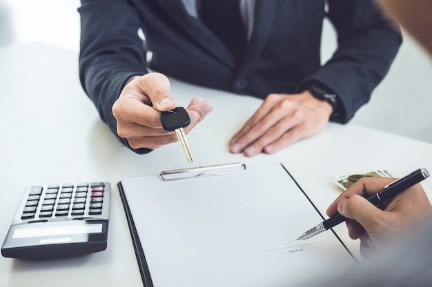 Salesman send key to customer after man signing car document contract good deal agreement