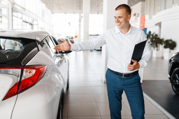 Salesman shows new car in showroom. male customer buying vehicle in dealership, automobile sale, auto purchase