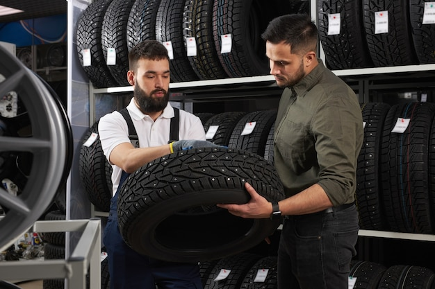 Salesman of tires talking about characteristic of product to customer came to look at assortment represented in auto service shop