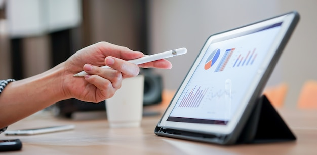 스타일러스 펜을 사용하여 태블릿 화면을 가리키는 세일즈맨은 회의 이벤트에서 회사의 이익을 보여줍니다.