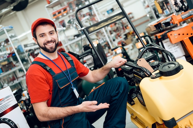 Salesman with plate compactor in power tools store