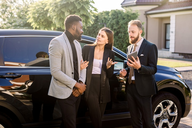 Salesman with tablet and clients, business couple, caucasian woman and african man, standing near new car outdoors. business people using tablet standing near black car outdoors