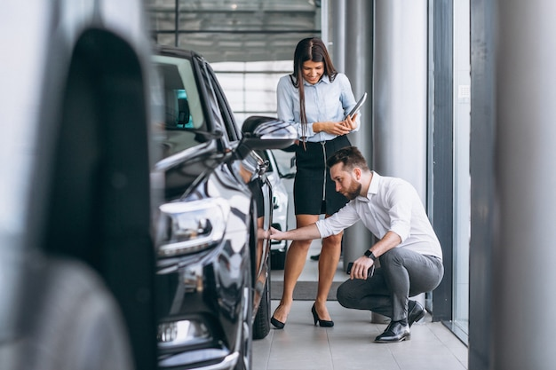 Salesman and woman looking for a car in a car showroom