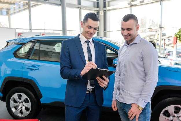 Salesman working with client in showroom, car buy operation