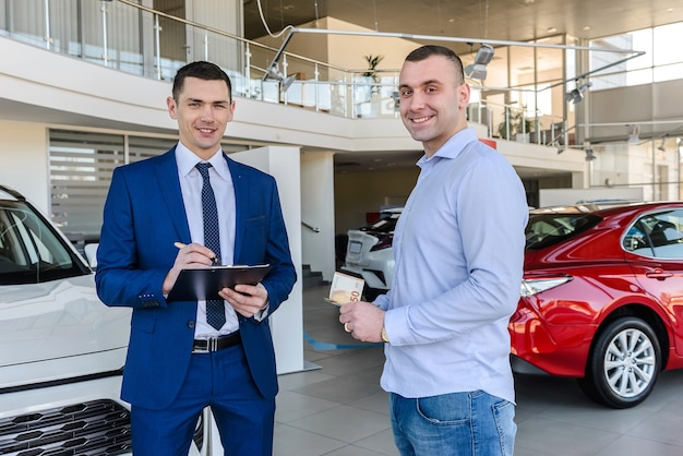 Salesman working with client in showroom car buy operation