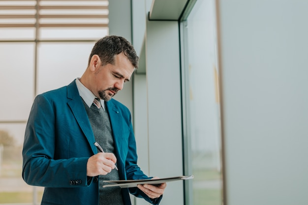 Salesman writing on clipboard in showroom.