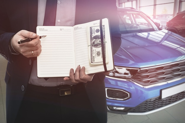 Salesman  writing on notepad  about sale or rent car