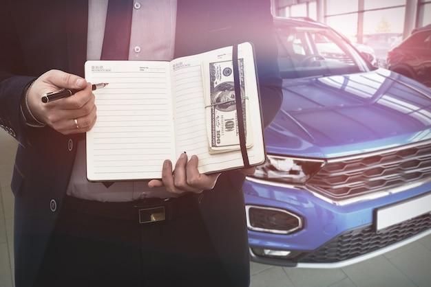 판매 또는 임대 자동차에 대 한 메모장에 쓰는 세일즈 맨