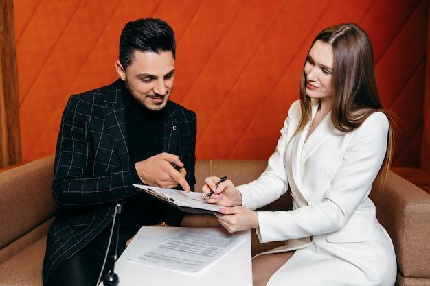 Продавцы позволяют клиентам-мужчинам подписать бизнес-концепцию договора купли-продажи и подписать договор.