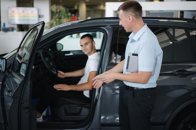 자동차 판매점에서 자동차를 판매하는 판매원 자동차 쇼룸에서 차를 선택하는 남자