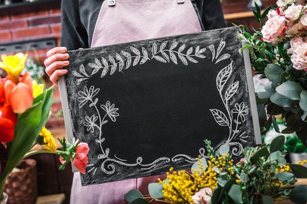 Salesperson showing empty blackboard among flowers