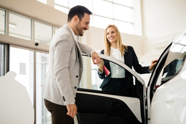 Salesperson showing vehicle to potential customer in dealership