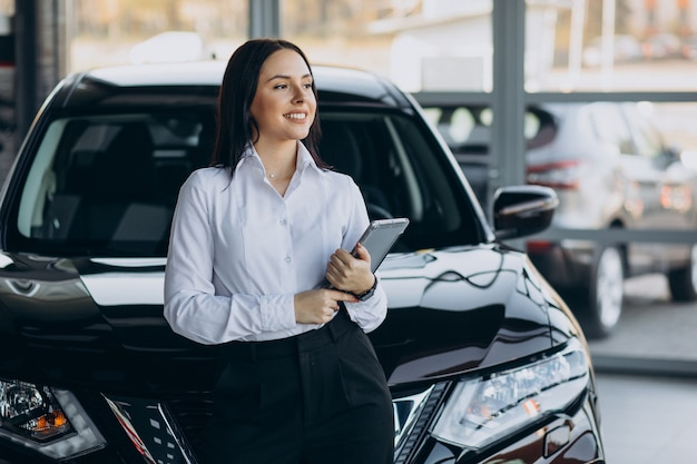 Saleswoman in car showroom selling cars
