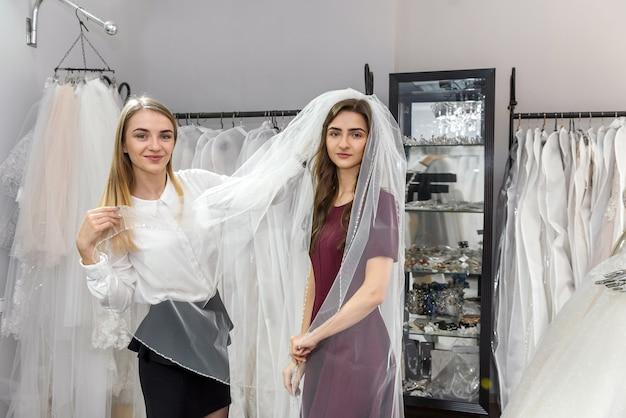 Продавщица примеряет фату для молодой невесты в магазине