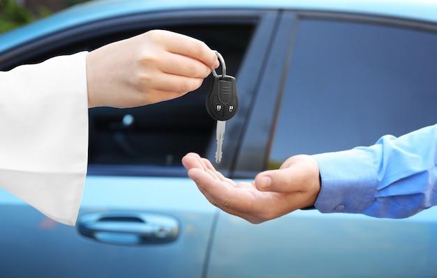 Продавщица дает ключ от машины клиенту на открытом воздухе