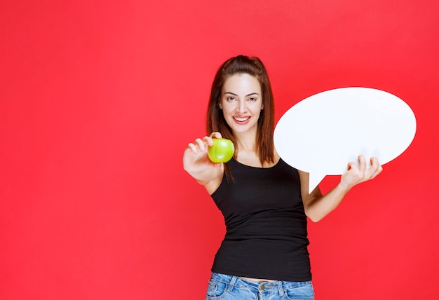 Saleswoman holding a green apple and an ovale info board and giving the apple to the customer