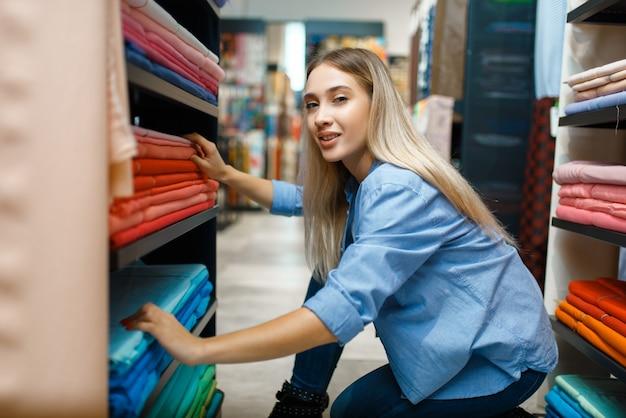 Продавщица измеряет ткань в текстильном магазине. полка с тканью для шитья