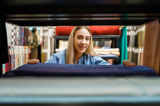 Продавщица измеряет ткань, просмотр через полку в текстильном магазине. витрина с тканью для шитья