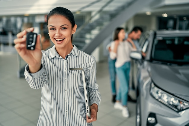 セールスウーマンがカメラに車のキーを表示します。ビジネスコンセプト、車の保険、車の売買、車の資金調達、車両販売契約の車のキー。