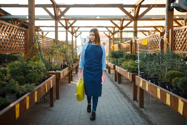 Saleswoman with watering can, shop for gardening