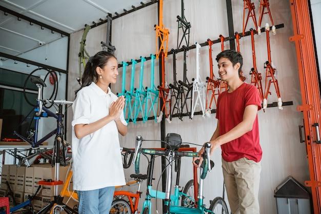 若い男性客が新しいバイクを選ぶように身振りで示す歓迎の手を持つセールスウーマン