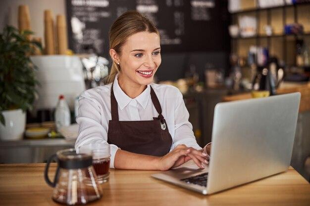 커피숍에서 노트북에서 일하는 판매원