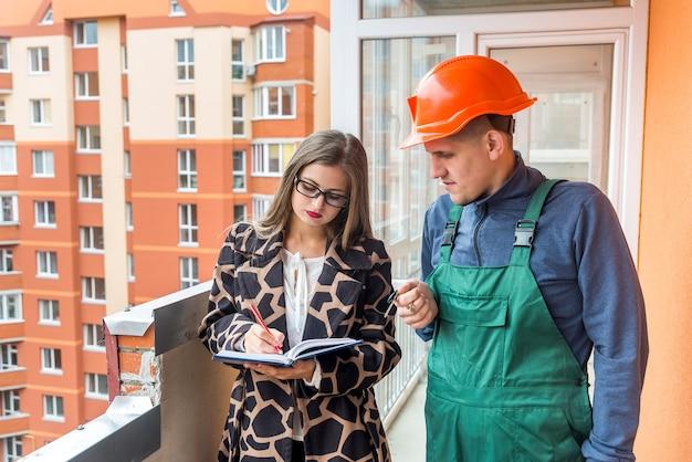 Продавщица, пишущая в блокноте и строитель, стоящий рядом