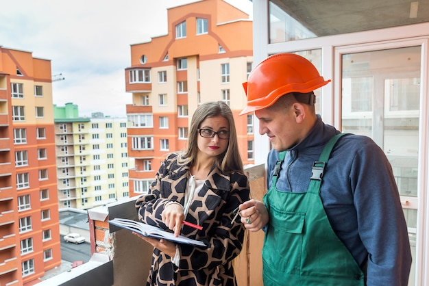 Saleswoman writing in notepad and builder standing near