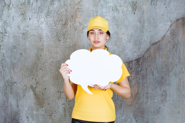A saleswoman in yellow uniform holding a cloud shape info board