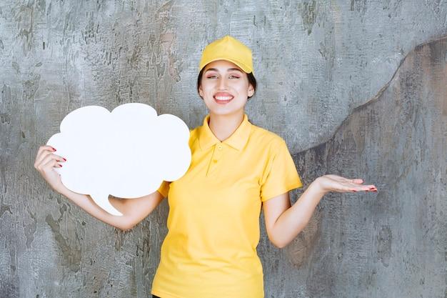 Una commessa in uniforme gialla con in mano una bacheca informativa a forma di nuvola.