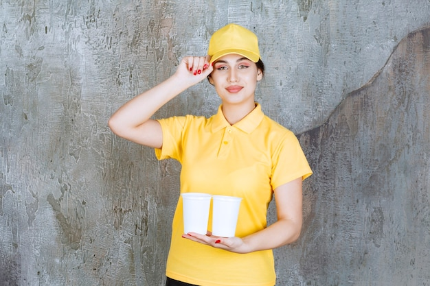 A saleswoman in yellow uniform holding two plastic cups of drink.