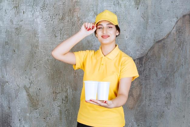Una commessa in uniforme gialla con in mano due bicchieri di plastica da bere