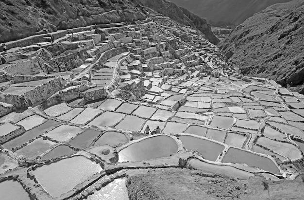 Salineras de maras historic salt mines in canyon of sacred valley of incas peru in monochrome