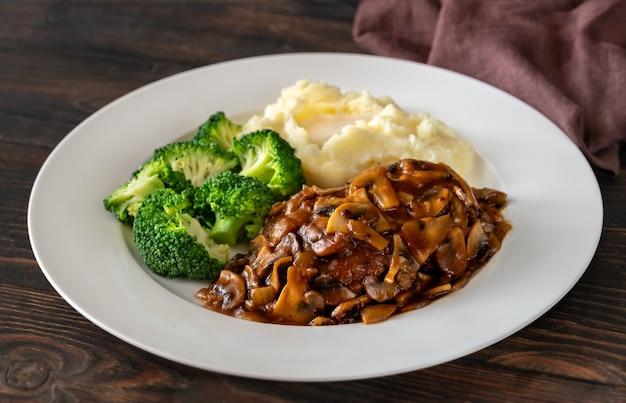 Salisbury steak with steamed broccoli and mashed potato